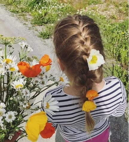Center Parted Hairstyle With Braided Ponytail And Flowers