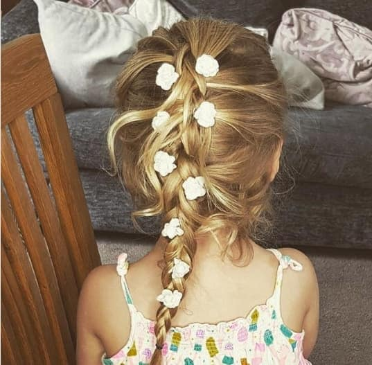 Combed Back Hairstyle With Braided Ponytail And Flowers